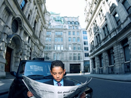 Stock Photo: 1527R-010053 Young Boy Dressed as a Businessman Stands in a City Road Reading a Newspaper