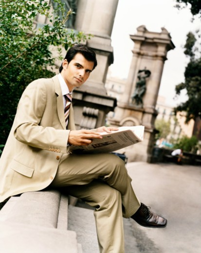 Businessman Sitting on Wall in a City Holding a Newspaper, Barcelona, Spain : Stock Photo