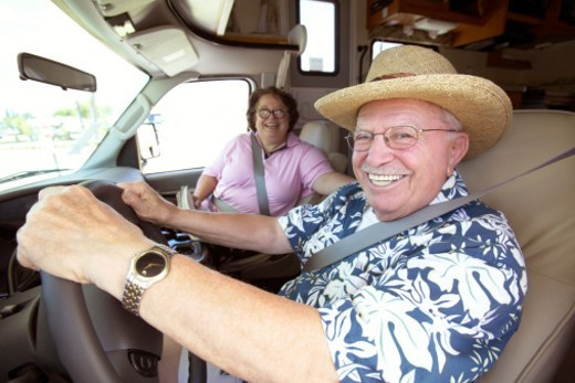 Senior Couple Sit in the Front Seat of a Motor Home, the Man Sitting at the Steering Wheel, Laughing : Stock Photo