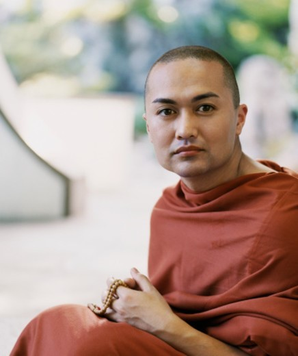 Portrait of a Male Buddhist Monk in an Orange Robe Holding Prayer Beads : Stock Photo