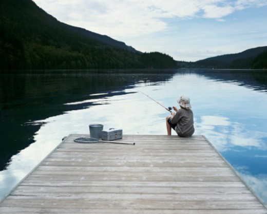 Rear View of a Young Boy Sitting at the Edge of a Boardwalk by a Lake, Fishing : Stock Photo