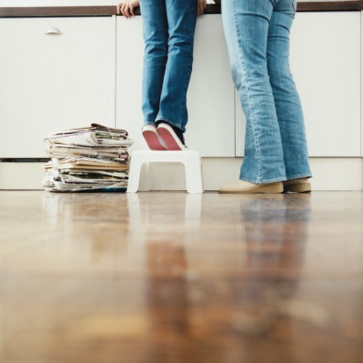 Stock Photo: 1527R-011421 Low Section of a Mother With Her Child Standing in a Kitchen, Child Standing on a Step Stool Next to a Tied up Bundle of Newspaper
