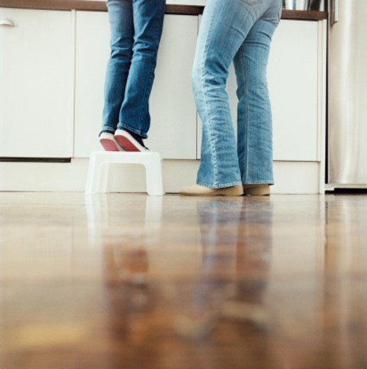 Stock Photo: 1527R-011422 Low Section of a Mother With Her Child Standing in a Kitchen, Child Standing on a Step Stool