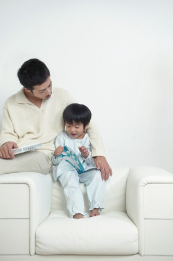 Stock Photo: 1527R-011754 Father and Son Reading a Book Together