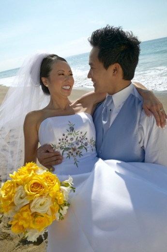 Stock Photo: 1527R-011796 Newlywed Groom Lifts Bride at Water's Edge on a Beach