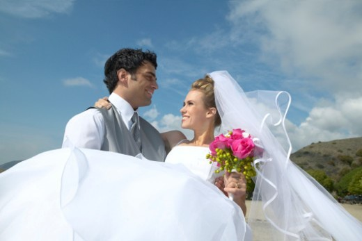Stock Photo: 1527R-011799 Newlywed Groom Lifts Bride With Bouquet