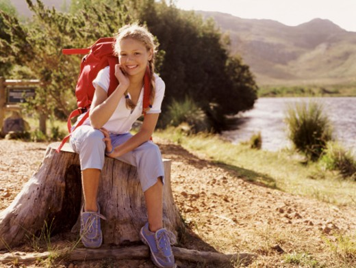 Stock Photo: 1527R-012134 Girl Outdoors Sitting on a Tree Stump
