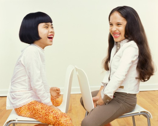 Two Young Girls Sit Face to Face on Chairs, Giggling : Stock Photo