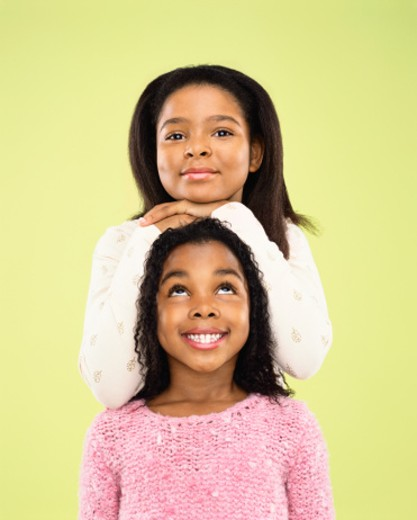 Stock Photo: 1527R-012407 Portrait of a Young Girl Leaning With Her Hands on Her Sister's Head