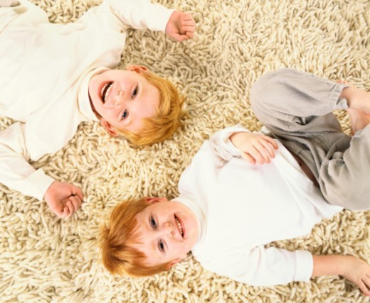 Two Young Brothers Lie Side by Side on a Carpet, Laughing : Stock Photo