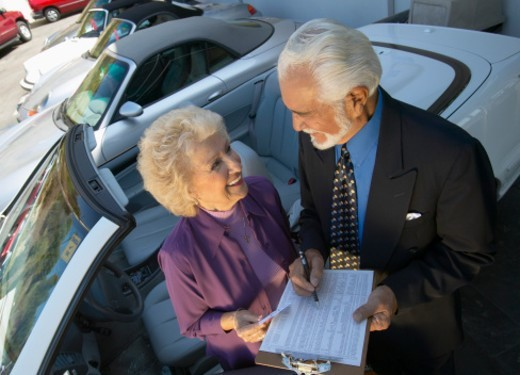 Stock Photo: 1527R-012609 Senior Salesman and Female Customer Stand Next to a New Convertible in a Car Showroom, Signing a Document on a Clipboard