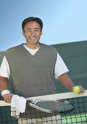 Stock Photo: 1527R-012792 Portrait of a Man Holding a Tennis Racket on a Tennis Court
