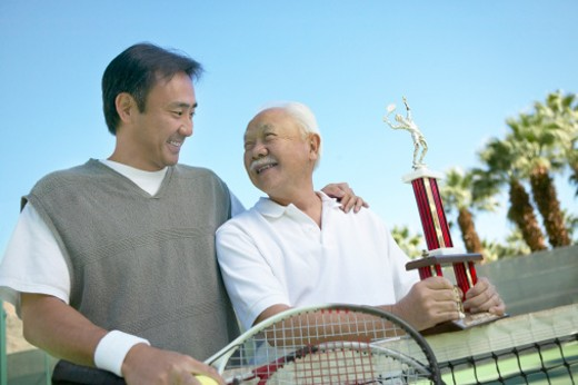 Father and Son Standing on a Tennis Court, with the Father Holding a Trophy : Stock Photo