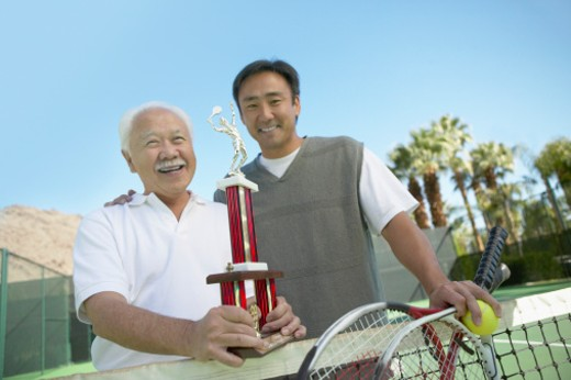Father and Son Standing on a Tennis Court with a Trophy : Stock Photo
