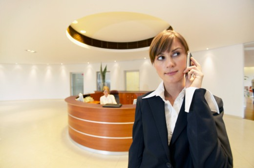 Young Businesswoman Using a Mobile Phone in an Office, with a Circular Reception Desk in the Background : Stock Photo