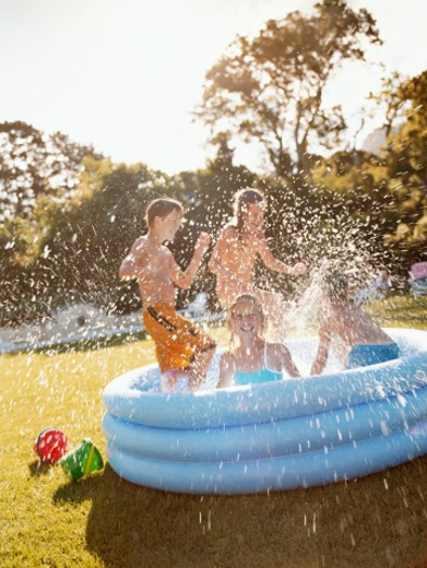 Four Children Splashing Around in a Paddling Pool : Stock Photo