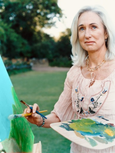 Senior Woman Painting Outdoors in a Garden : Stock Photo