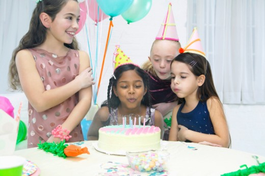 Stock Photo: 1527R-014097 Small Group of Girls in Party Hats Blow Out Candles on a Birthday Cake