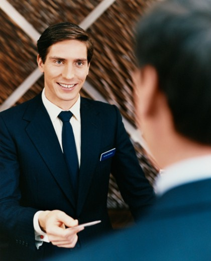 Stock Photo: 1527R-015271 Male Hotel Receptionist Hands a Credit Card Back to a Customer