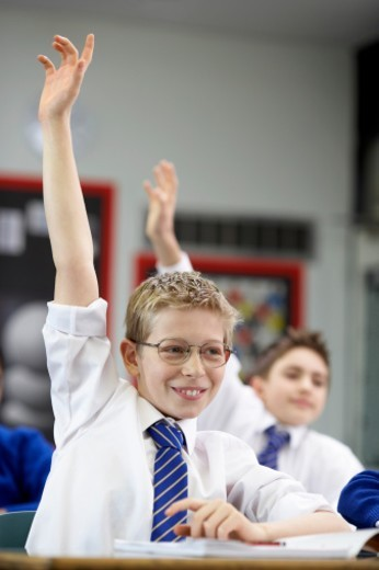 Stock Photo: 1527R-015382 Schoolboys in a Classroom with Their Hands Raised