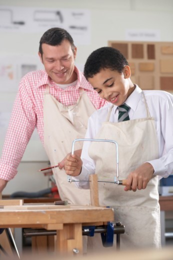 Male Secondary School Teacher Watching a Schoolboy Sawing a Piece of Wood with a Hacksaw : Stock Photo