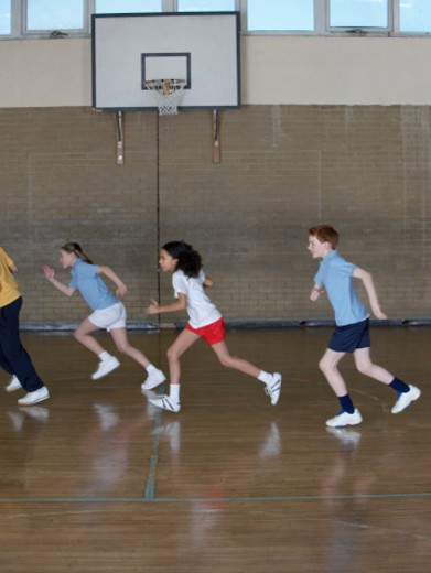Stock Photo: 1527R-015432 Four School Children Running in a School Sports Hall