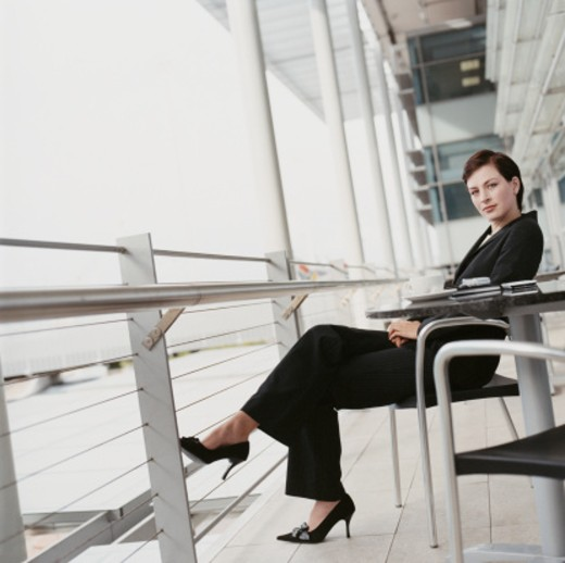 Businesswoman Sitting on the Balcony of a Modern Building : Stock Photo