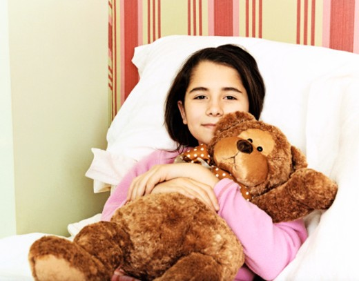 Portrait of a Girl Lying in Bed and Holding a Teddy Bear : Stock Photo