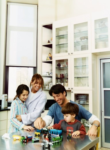 Father and Son in a Kitchen Playing With Toy Trains and Mother and Daughter Watching : Stock Photo
