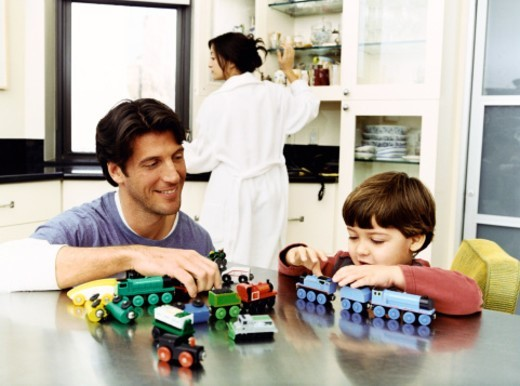 Father With His Son Playing With a Toy Train Set on a Metallic Kitchen Counter and a Woman in the Background : Stock Photo