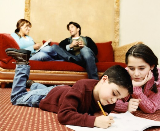 Stock Photo: 1527R-016034 Children Lying on a Living Room Carpet, Boy Drawing and His Sister Watching and Their Parents in the Background on a Sofa