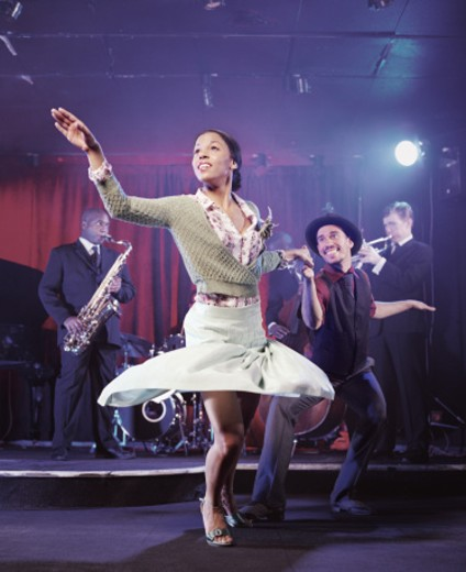Stock Photo: 1527R-016043 Man and Woman Dancing in a Nightclub and a Jazz Band on Stage in the Background