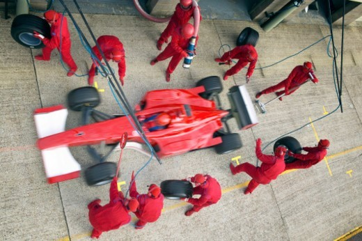 Elevated View of Mechanics Maintaining a Red Formula One Car at a Pit Stop : Stock Photo