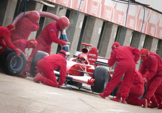 Stock Photo: 1527R-016064 Mechanics Maintaining a Red Formula One Car at a Pit Stop