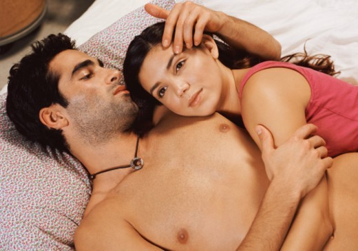 Stock Photo: 1527R-017055 Couple Laying on a Bed, Affectionate Man With His Arm Around His Girlfriend