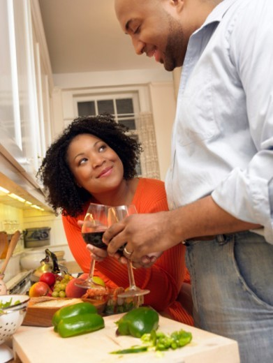 Couple Stand by a Kitchen Counter Preparing Food and Making a Toast With Glasses of Red Wine : Stock Photo