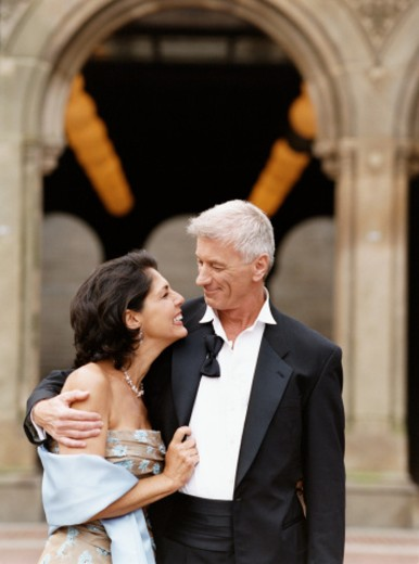Stock Photo: 1527R-017562 Mature Couple in Evening Wear Stand Outdoors, Embracing and Smiling at Each Other