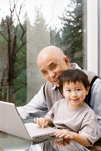 Stock Photo: 1527R-017782 Senior Man Sits at a Table With His Young Grandson on His Lap, Using a Laptop