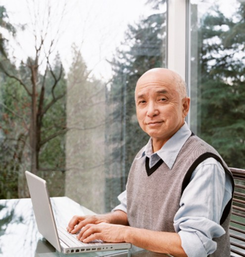 Senior Man Sits at a Table by a Window Using a Laptop : Stock Photo