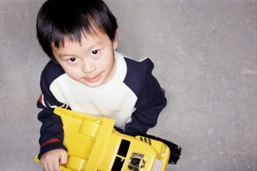 Portrait of a Young Boy Holding a Toy Car : Stock Photo