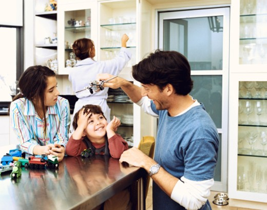 Father Playing With Toys With His Son and Daughter in a Kitchen, and Mother in the Background : Stock Photo