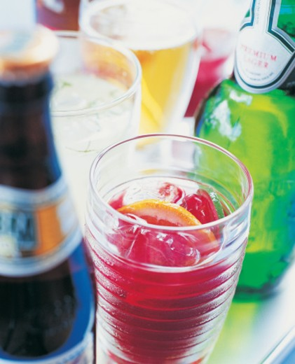 Stock Photo: 1527R-01883 Glass of Punch With Ice Cubes and Various Bottles