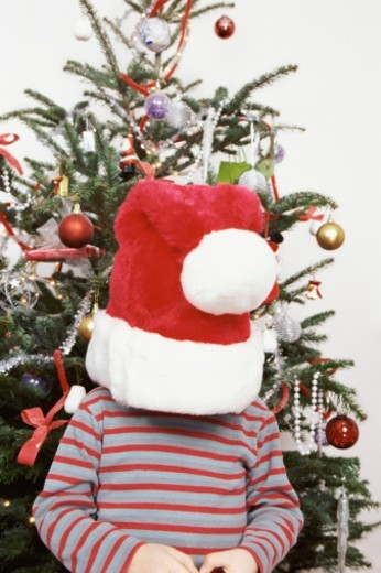 Stock Photo: 1527R-019122 Child Wearing an Oversized Santa Hat