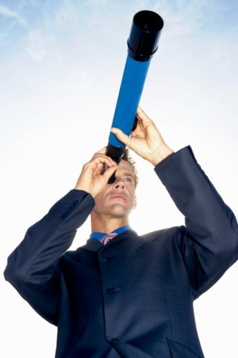 Stock Photo: 1527R-019371 Low Angle View of a Businessman Looking Through a Telescope