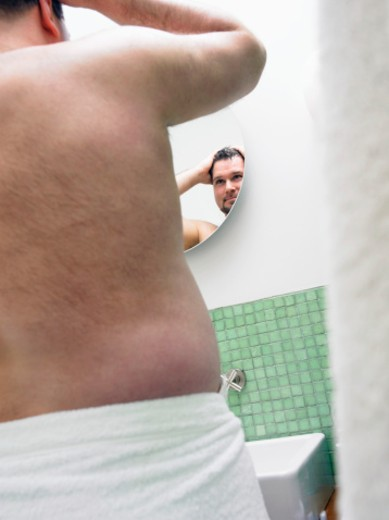 Stock Photo: 1527R-019492 Rear View of an Overweight Man Wrapped in a Towel, Looking at a Bathroom Mirror