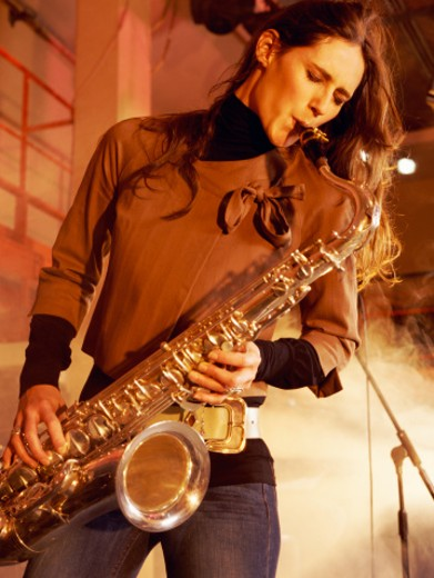 Stock Photo: 1527R-019539 Woman Stands on a Smoky Stage Playing a Saxophone With Passion