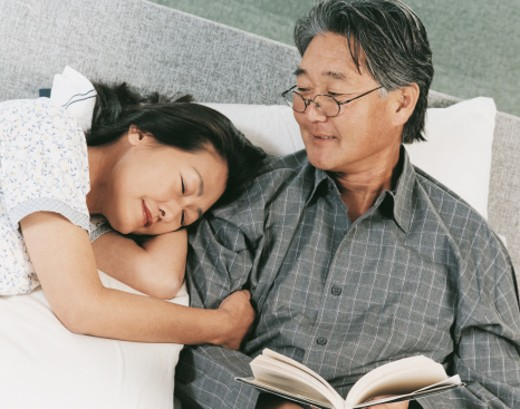 Mature Couple in Bed With the Man Reading and the Woman Lying with Her Arm Around Him : Stock Photo