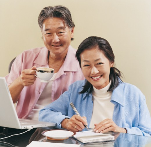 Portrait of a Couple Sitting at a Desk at Home and Writing Out a Cheque : Stock Photo