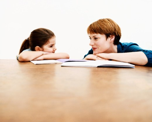 Stock Photo: 1527R-020275 Woman Crouches at a Table With Her Young Daughter, Teaching Her From Books
