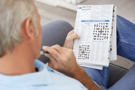 Stock Photo: 1527R-020412 Senior Man Contemplating a Newspaper Crossword
